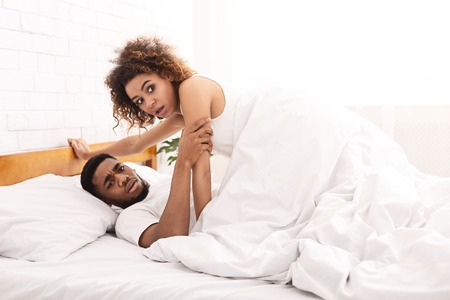 Betrayal. Shocked african-american couple lying in bed together, copy space