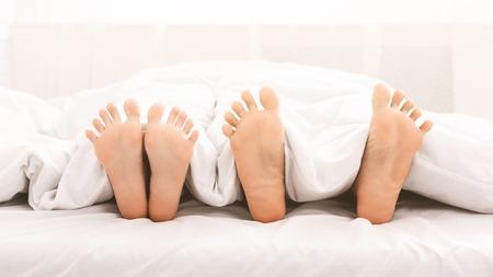 Pies descalzos de pareja en la cama. Pareja amorosa acostada bajo una manta blanca, panorama, espacio de copia