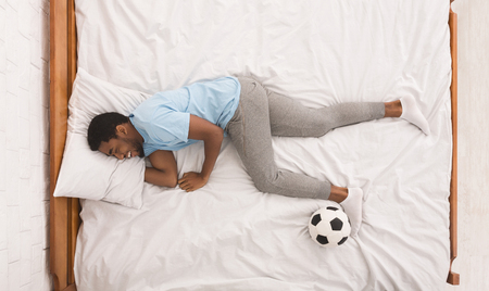 Cheerful african-american sportsman sleeping with soccer ball on bed, top view, copy space