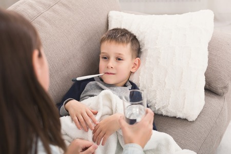 Little boy measuring temperature with thermometer, sister bring glass of water