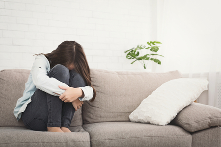 Unhappy girl sitting on sofa feeling lonely and sad, hugging knees and crying, copy space