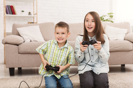 Brother and sister playing online video games together, sitting on floor at home Stock Photo