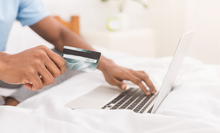 Online shopping. African-american millennial guy making purchases in internet, using laptop and credit card to pay, copy space