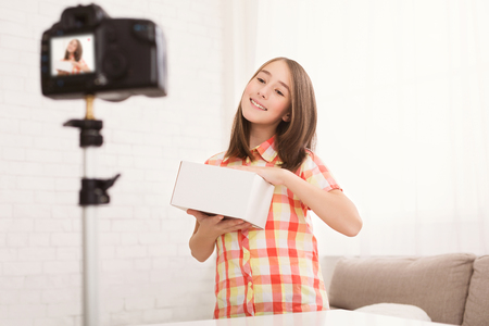 Pre-teen girl showing box and making guesses about its content, recording video blog Imagens