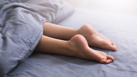 Beautiful female legs with smooth sole lying in bed under blanket, panorama, closeup