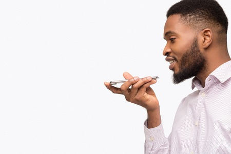 African-american man using voice assistant on mobile phone, talking to smartphone, isolated on white background, copy space