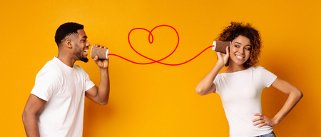Love message. Lovely african-american couple talking on a tin phone, orange background, panorama Standard-Bild