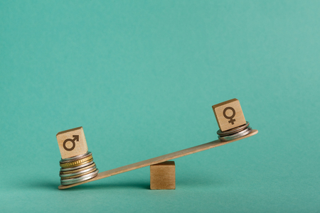 Gender pay gap. Wooden cubes with male and female gender signs on seesaw with different stacks of coins, men outweigh, copy space