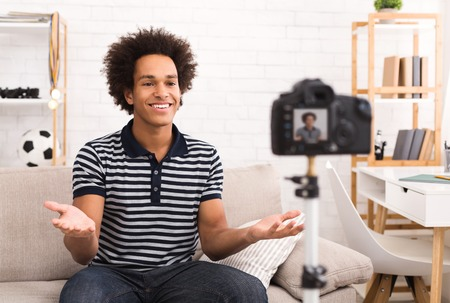 Young male blogger greeting with his viewers while recording video at home Stock fotó