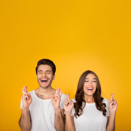 Couple close eyes and cross fingers with hope against yellow background, crop, copy space