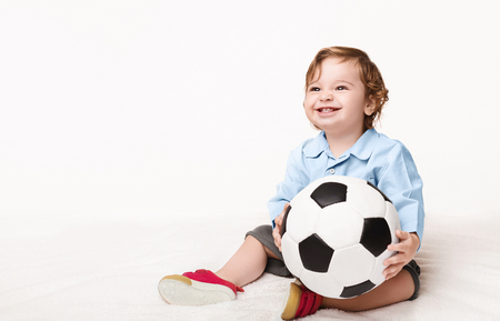 Little football fan. Laughing baby boy holding soccer ball and looking at copy space, panorama, white background