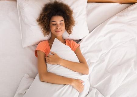 Mattinata. Donna afroamericana che abbraccia il cuscino a letto, vista dall'alto