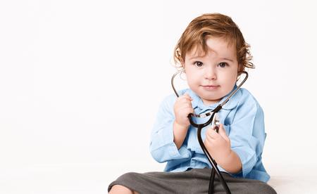 Wie ein Arzt. Ernstes Baby, das mit Stethoskop auf weißem Hintergrund sitzt, Panorama mit Kopienraum