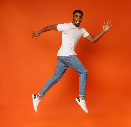 Funny young black millennial guy walking on air, jumping on orange studio background, smiling at camera Stockfoto