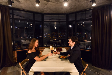 Romantic couple on dating in restaurant on panoramic window background with night city view Banco de Imagens