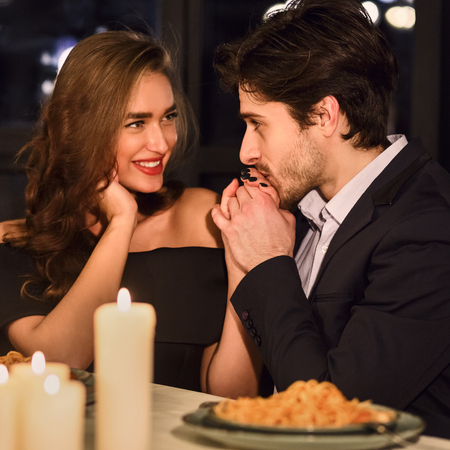 Handsome man kissing hand of his girlfriend in restaurant during romantic dinner. Tender feelings concept Banco de Imagens