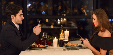 Man and woman do not communicate to each other and using their smartphones during dinner. Lack of communication in couple concept Stock Photo