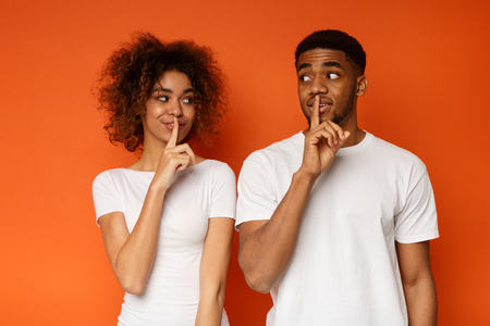 Shhh, its our secret. Millennial african-american man and woman holding fingers on lips and looking at each other mysteriously, orange studio background Standard-Bild