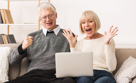 Excited senior couple celebrating victory, winning online auction bid looking at laptop Stok Fotoğraf