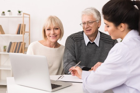 Elderly couple discussing treatment plan with doctor at home Standard-Bild