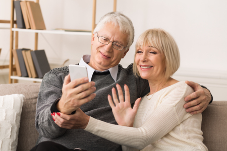 Senior couple making video call from smartphone, having rest at home