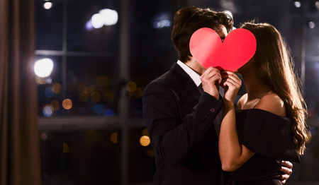 Kissing couple behind a paper heart. Celebrating Saint Valentines Day concept, copy space.