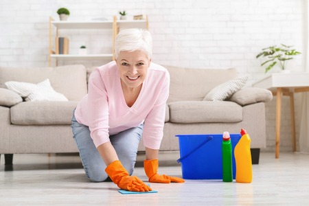 Smiling mature housewife cleaning floor with detergents and rag at home, wearing protective gloves, copy space 免版税图像