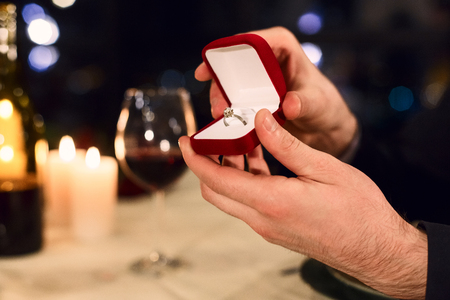 Mans hands holding box with ring making proposal. Marry me concept
