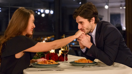 Handsome man kissing hand of attractive woman in restaurant during romantic date. Happy dating concept