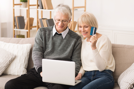 Happy older couple doing online shopping on laptop at home