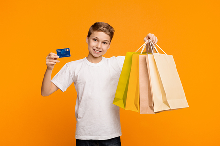 Young shopper. Pleased caucasian boy showing credit card and shopping bags, orange studio background Фото со стока