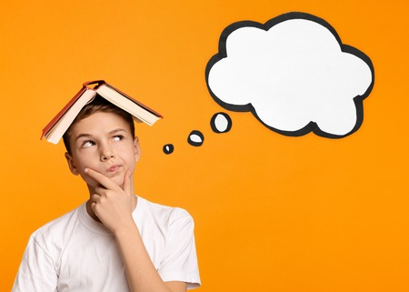 Cute boy with book on head thinking and doubtfully looking at thought bubble, orange background, copy space