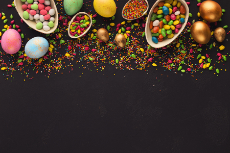 Border of easter eggs and scattered colorful candies on black background, copy space Stock Photo