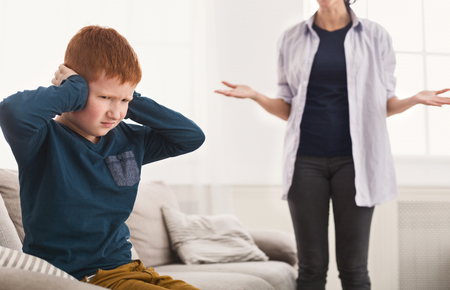 Educational process. Upset boy pouting and close ears when mother scolding him for mischief Stock Photo