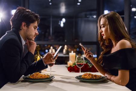 Man and woman do not communicate to each other and using their smartphones during dinner. Lack of communication in pair concept Stock Photo