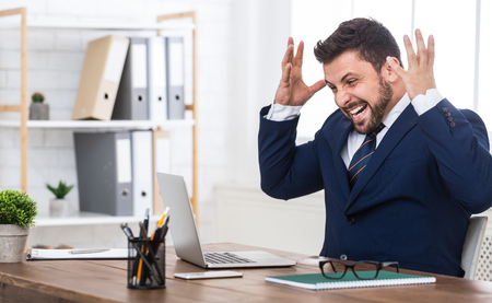 Happy man completed task and triumphing with raised hands, sitting at workplace in office, empty space Stok Fotoğraf