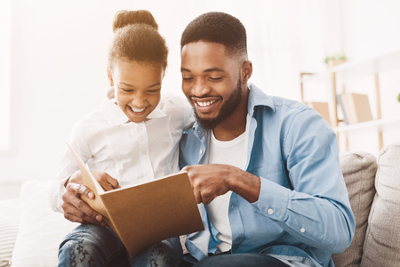 Little girl and father enjoying reading book together at home