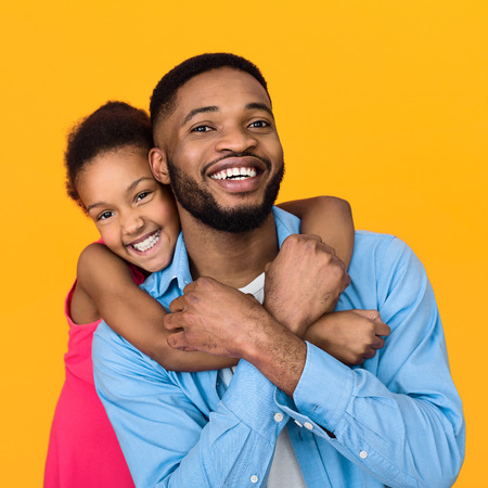 Father giving piggyback ride to his daughter against yellow background, crop