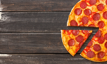 Pizza Diabolo slice on wooden background, top view, copy space. Pizza to go concept Banque d'images - 116330388