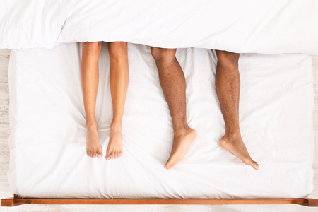 African-american couple legs under duvet laying on bed, top view