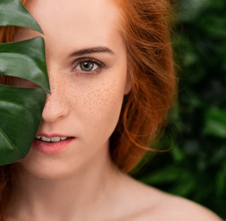 Natural cosmetics and skincare. Beautiful redhead woman with freckles covering half of face with monstera leaves Фото со стока