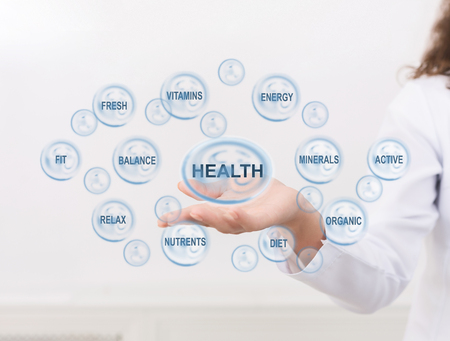 Doctor showing health caring icons and other medical signs on virtual screen Фото со стока