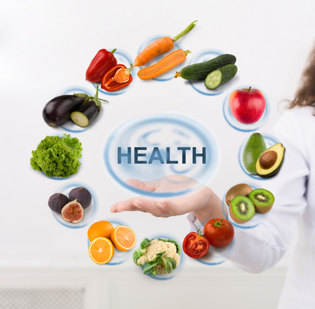 Doctor dietitian showing Health sign with fruits and vegetables icons on virtual screen