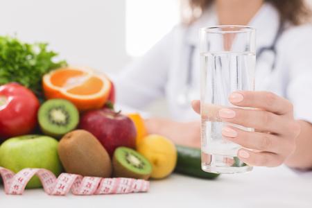 Concepto de desintoxicación y limpieza. Médico nutricionista sosteniendo un vaso de agua en su oficina, espacio libre Foto de archivo