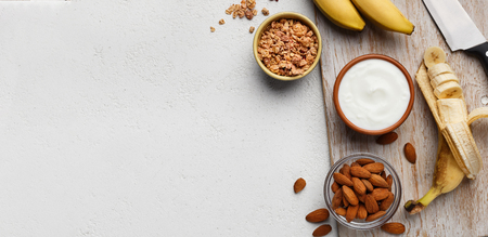 Bowls with yogurt, granola and almond on white background, top view, copy space. Organic breakfast recipe concept