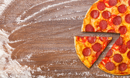 Cooked pizza Diabolo slice and flour on wooden background, top view. Homemade pizza concept Banque d'images - 117166944