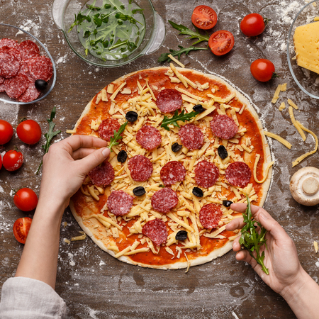 Chef decorating pizza with rocket salad, salami and other ingredients, top view, crop Archivio Fotografico