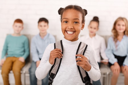 African-american school girl carrying backpack with schoolmates on background