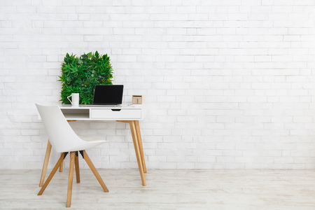 Scandinavian and minimalistic style. Modern workplace with laptop and flowerbox, empty space