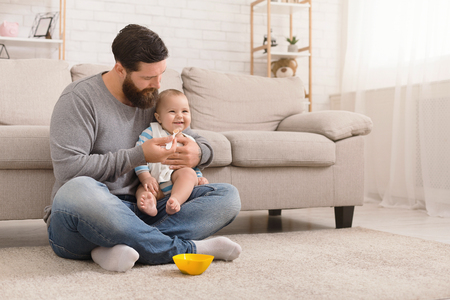 Time for snack. Young millennial man feeding his little baby son with porridge, sitting on floor at home, free space
